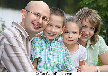 family with two children in park near pond. focus on little girl\'s face.