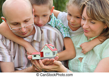 family with two children is keeping wendy house in their hands and looking at it. focus on wendy house. faces in out of focus.
