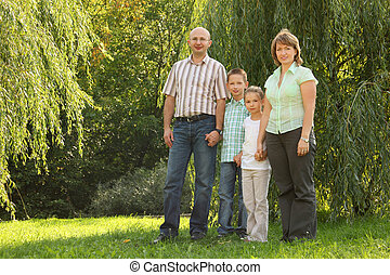 family with two children is standing near osier in early fall park.