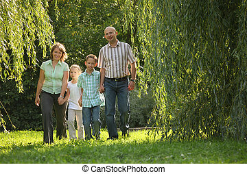 family with two children is walking in early fall park. dad and mom is smiling