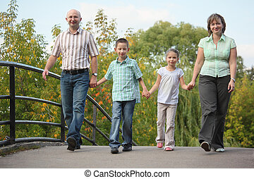 family with two children is walking on bridge in early fall park. family is handies.