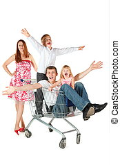 family with two children. joyful father with son and daughter is sitting in shopping basket. mother is standing behind shopping basket. isolated.
