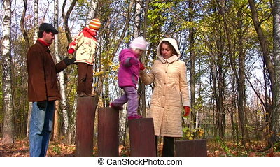 family with two children play in park on stiles