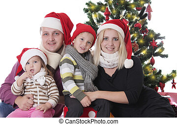 Family with two children sitting under Christmas tree
