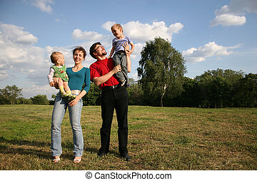 family with two children stand on meadow and trees