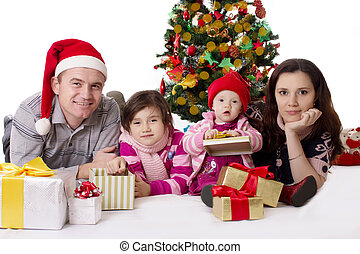 Family with two little daughters lying under Christmas tree