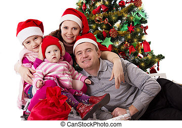 Family with two little daughters under Chritmas tree