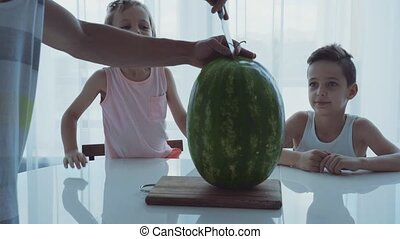 Family with two little funny children sitting at a dinner table. Dad cuts a large watermelon.