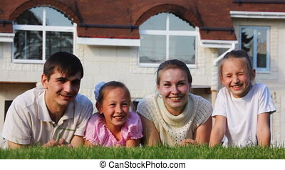 family with two little girls lies on lawn and smiles