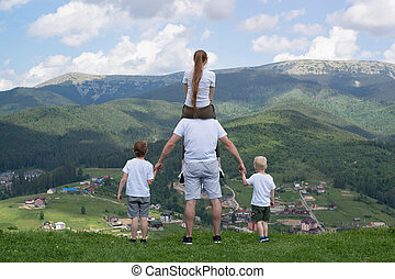 Family with two sons stands on a hill looking at the mountains. Summer day. Back view.