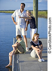 Family with two teenage children on dock by water