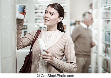 Stylish beaming green-eyed family woman shopping in pharmacy store