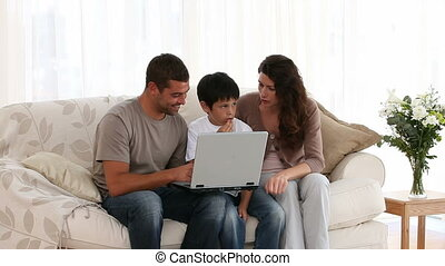 Family working on a laptop together sitting on the sofa of...