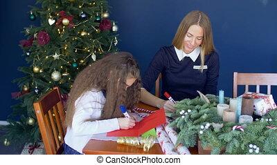 Family writing traditional greeting cards for xmas - Joyful...
