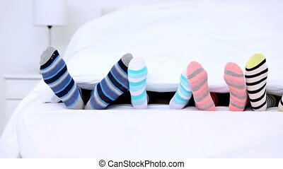 Familys feet in stripey socks kicking under the covers at...