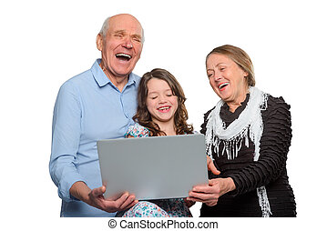 Family's having fun with notebook. Young girl and her granparents