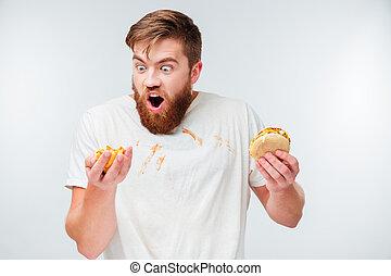 faminto, homem enfrentado, em, imundo, camisa, comer, hamburgers