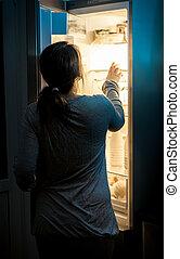 faminto, mulher olha, em, refrigerador, em, noite atrasada