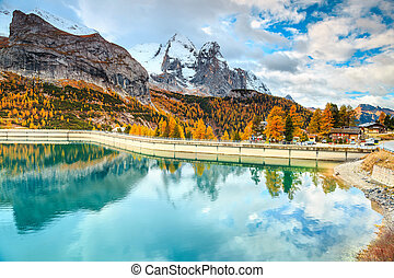 Famous alpine lake with snowy peaks in background, Dolomites, Italy