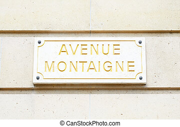 Famous Avenue Montaigne street sign in golden letters in Paris, France