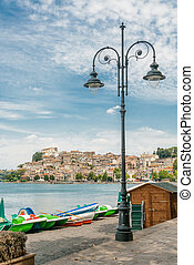 Famous beach on the Bracciano Lake with Anguillara Sabazia on Background, Rome, Lazio Region of Italy