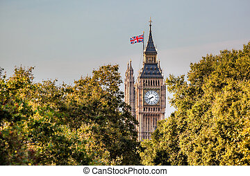 Famous Big Ben clock against trees in London, England, UK