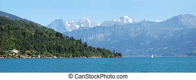Famous Eiger, Moench and Jungfrau mountain peaks and the lake Thun. Switzerland