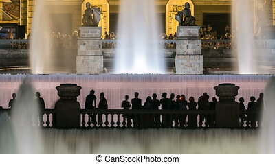 Famous light show and magic fountains timelapse in front of the National Art Museum at Placa Espanya in Barcelona at night, Catalonia, Spain. View with people silhouette on bottom. 4K