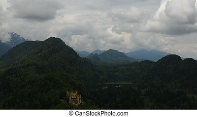 Famous Neuschwanstein Castle with scenic mountain landscape and cloudy sky near F?ssen, Bavaria, Germany