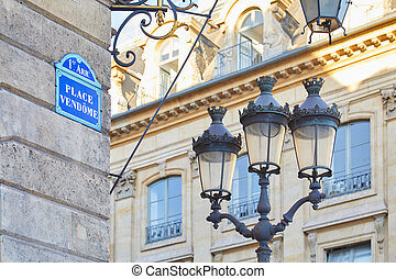 Famous Place Vendome corner with street sign and lamp in Paris, France.