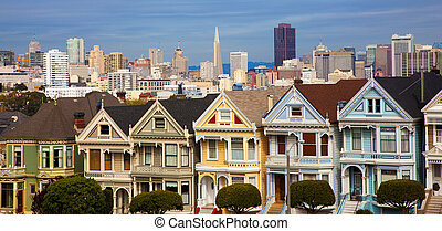 Famous row houses in San Francisco Ca. with skyline behind -...