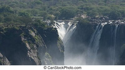 famous Ruacana waterfalls on the Kunene River, Northern Namibia border, Africa wilderness landscape, Waterfall is full of water after rain season.