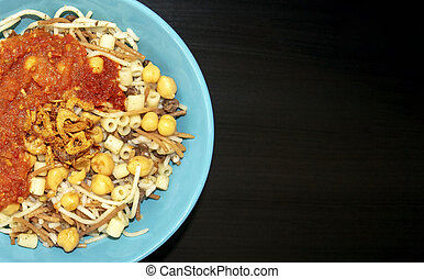 Famous traditional Arabic, Egyptian dish - Koshari. National Kushari in a turquoise plate on dark wooden background with copy space.
