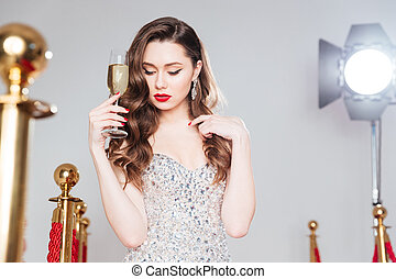Famous woman holding glass of champagne