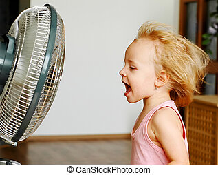 Fan - A little girl standing in front of fan