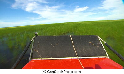 Fan Boat Cruising Through Swamp - Handheld, medium wide shot...