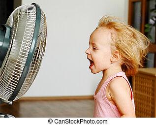 Fan - A little girl standing in front of fan