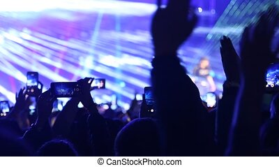 Fan taking photo and video of concert at festival.
