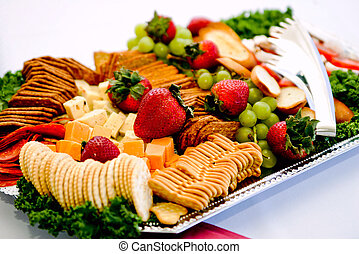 an appetizer tray with crackers, berries, grapes and other items
