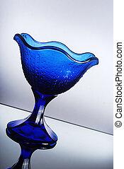 Fancy blue dessert glass on reflective surface