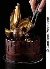 Fancy chocolate cake, isolated, black background. The hand of the pastry chef is present in the frame