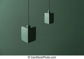 Fancy dark green metal lamps hanging on colorful background in studio