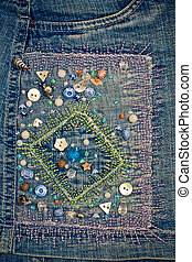 Handmade embroidery with buttons on the blue jeans