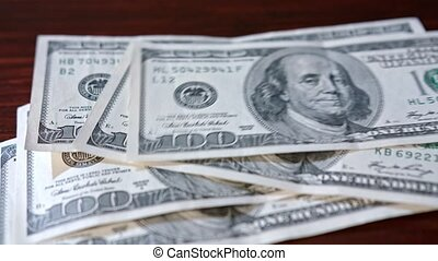 Fanned Pile of Hundred Dollar Banknotes on a Table - Fanned...