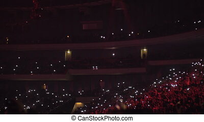 Fans at concert waving lanterns in the dark