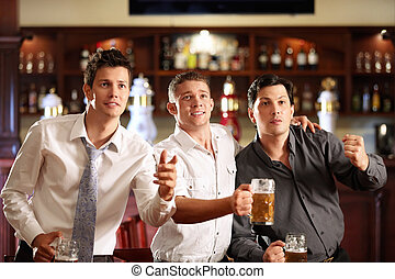 Fans at the bar - Young men with a beer watching the match ...
