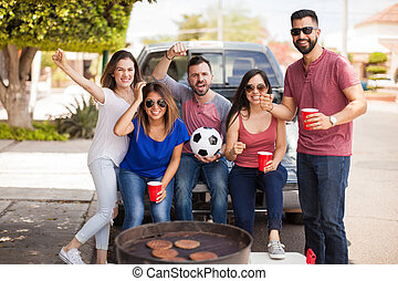 Fans of a soccer team grilling burgers at the game