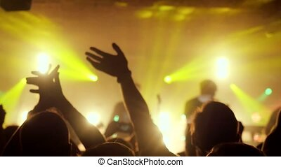 Fans waving their hands at rock concert in a night club. 3840x2160