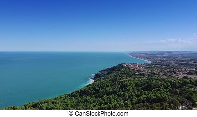 Fantastic aerial view of Italian coastal zone with azure sea, forest and city suburbs in the background