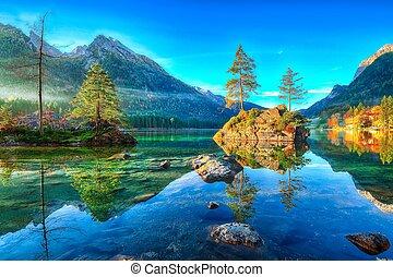 Fantastic autumn sunrise of Hintersee lake. Beautiful scene of trees on a rock island.